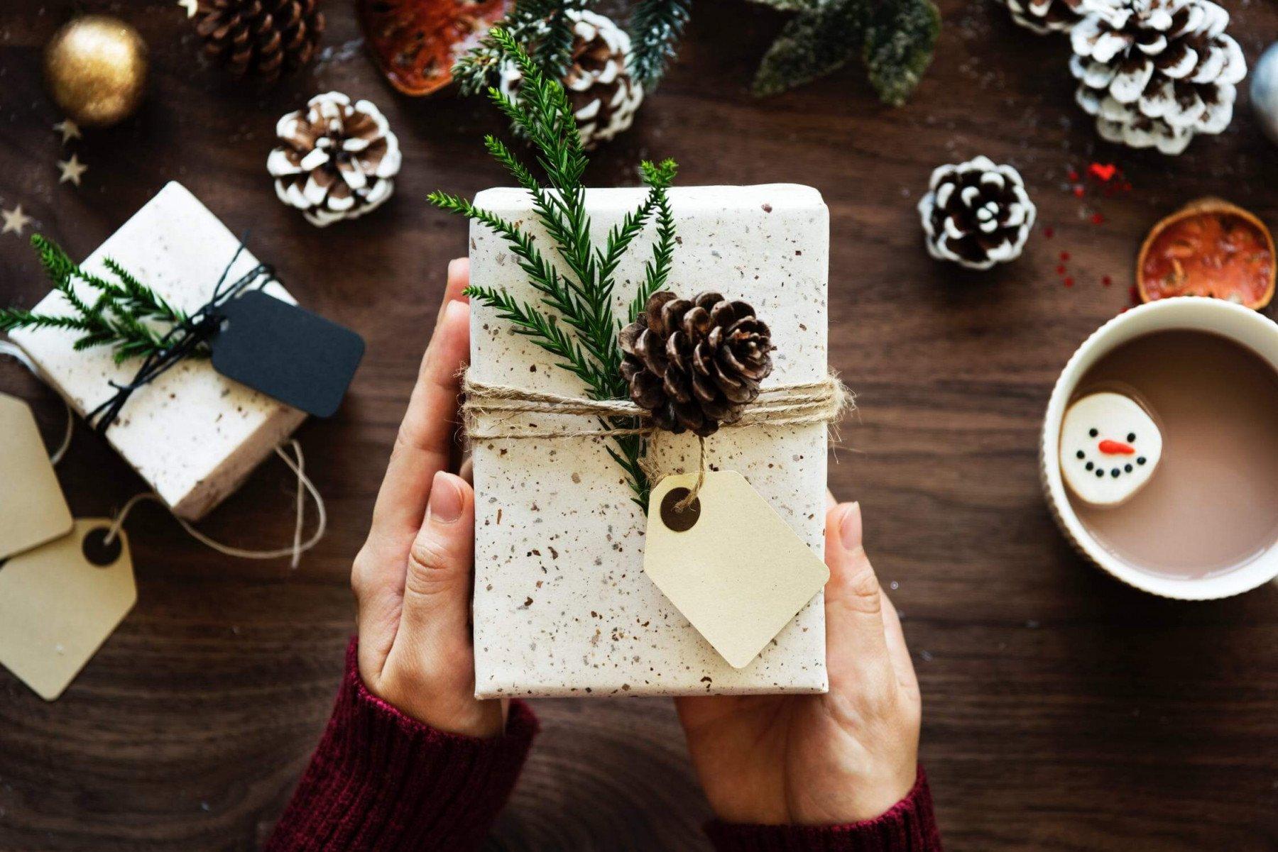 En julklapp inslagen med grankvist och kotte