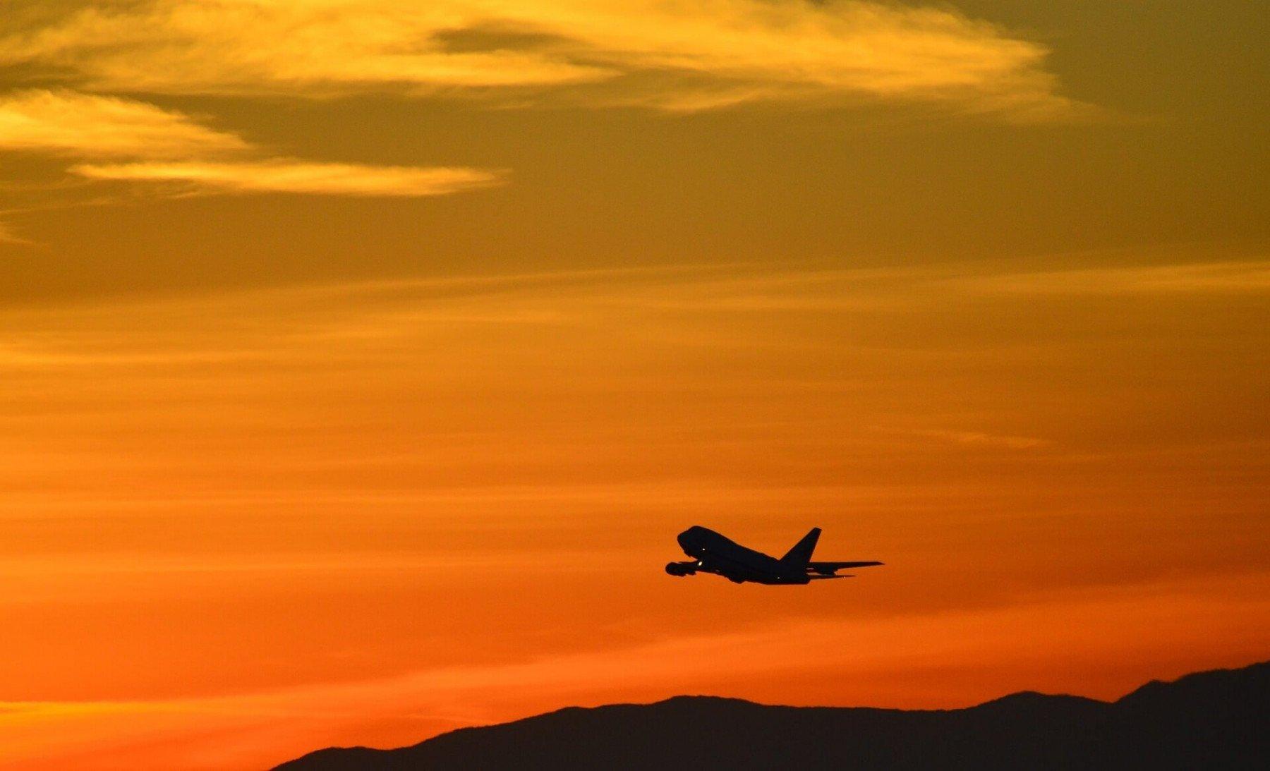 Flygplan som flyger över solnedgång