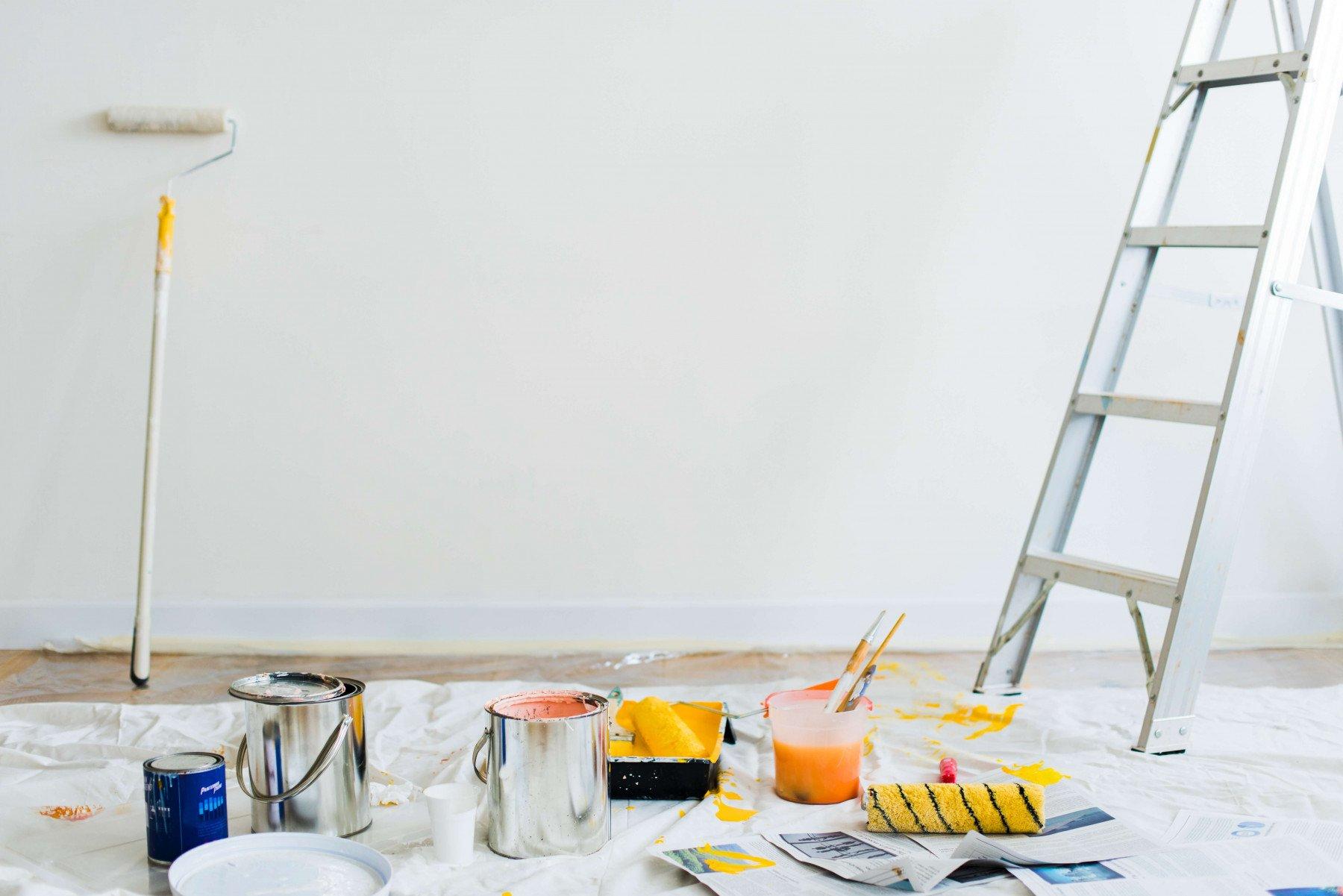 Renovering pågår med en massa målarpenslar och färgburkar