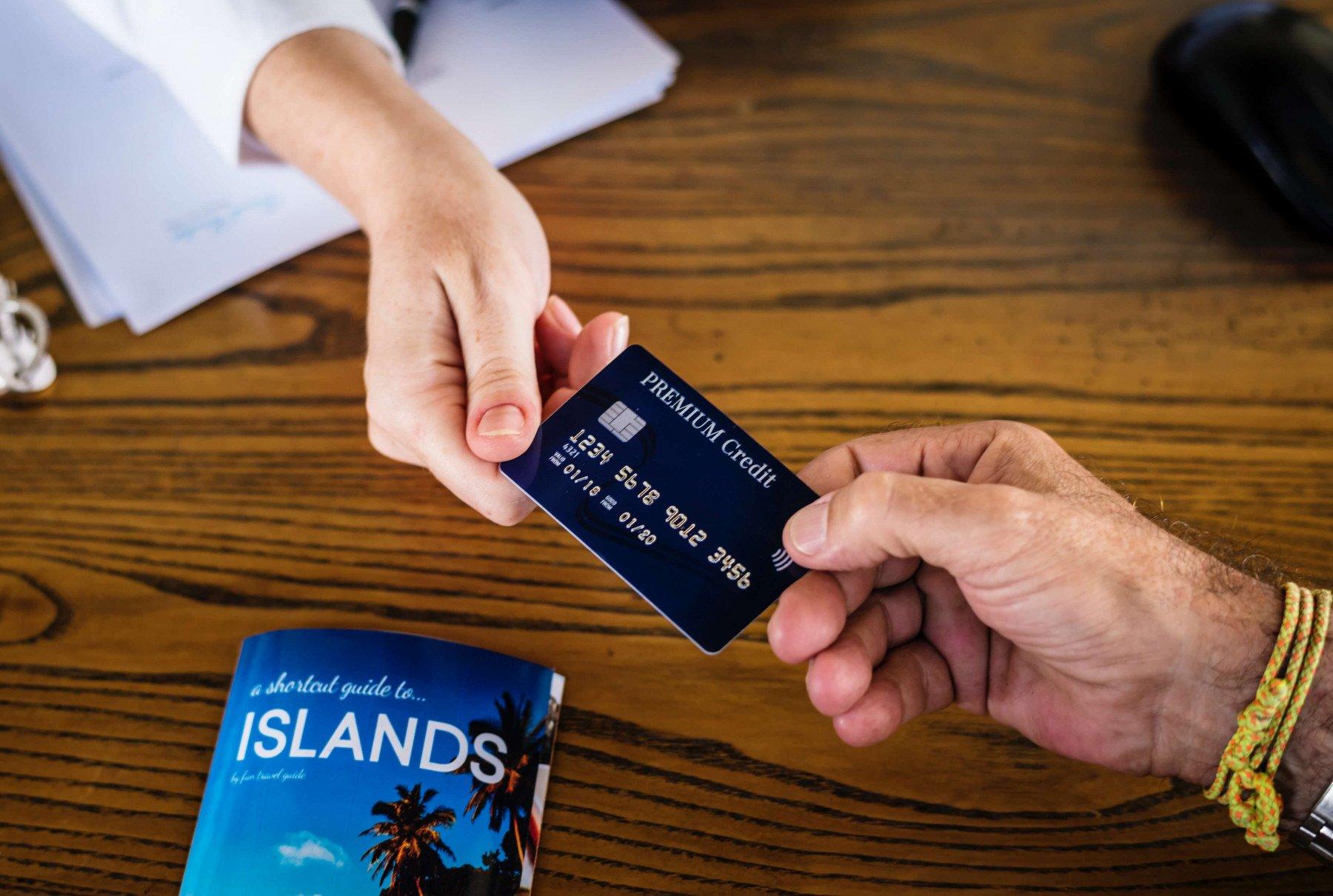 En man och en kvinna håller ett kreditkort i var sitt hörn.