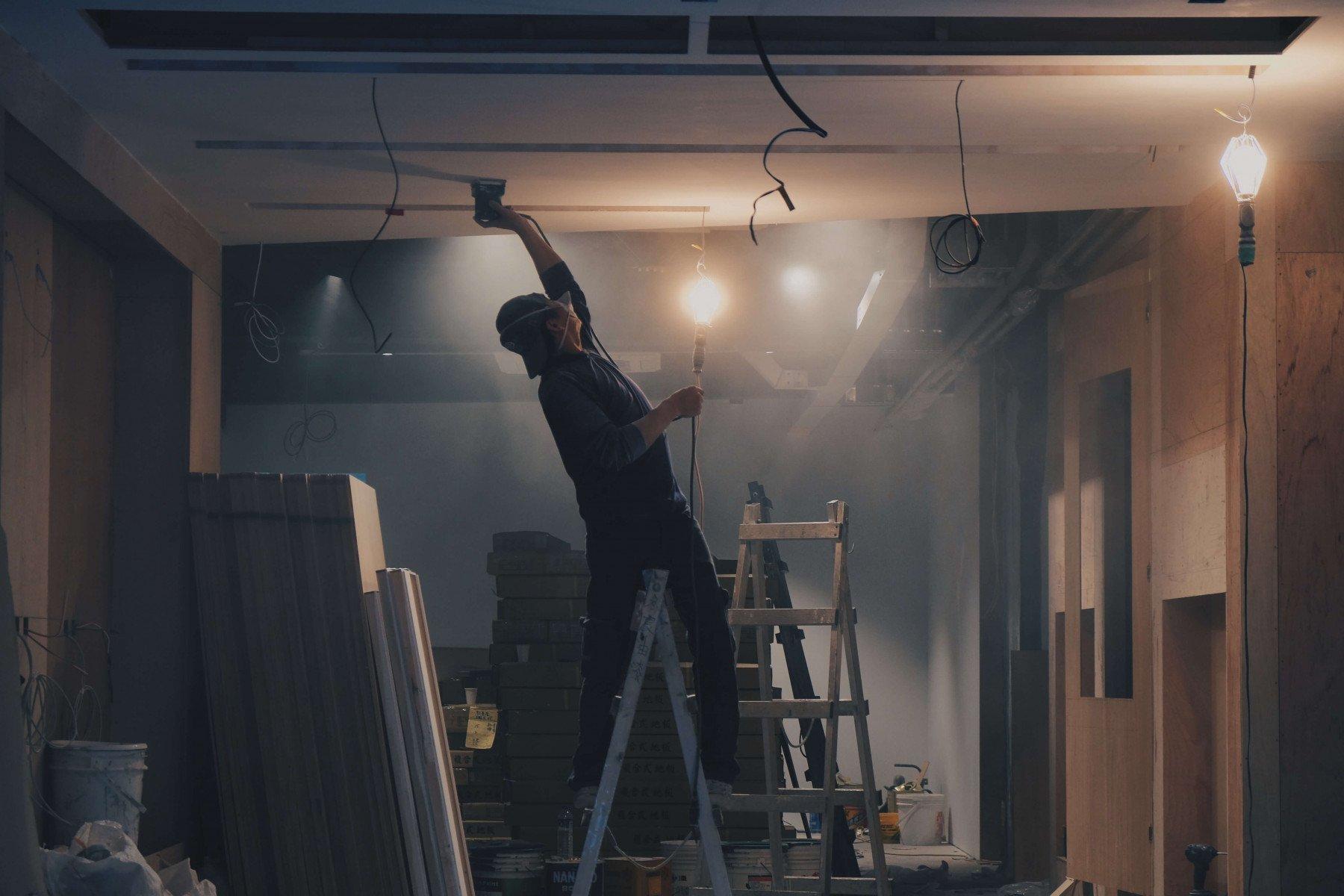 Person står på en stege och målar taket