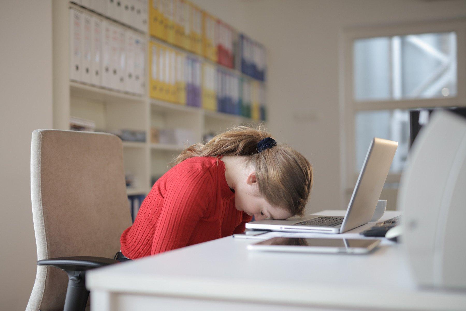 Person sitter vid en dator och lutar sitt huvud mot datorn.