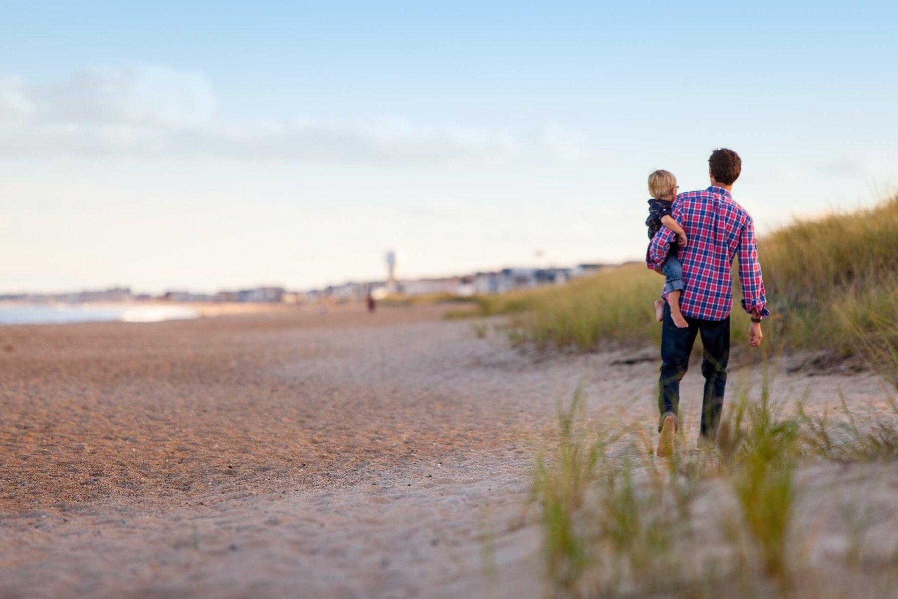 En förälder bar sitt barn i famnen längs en strand