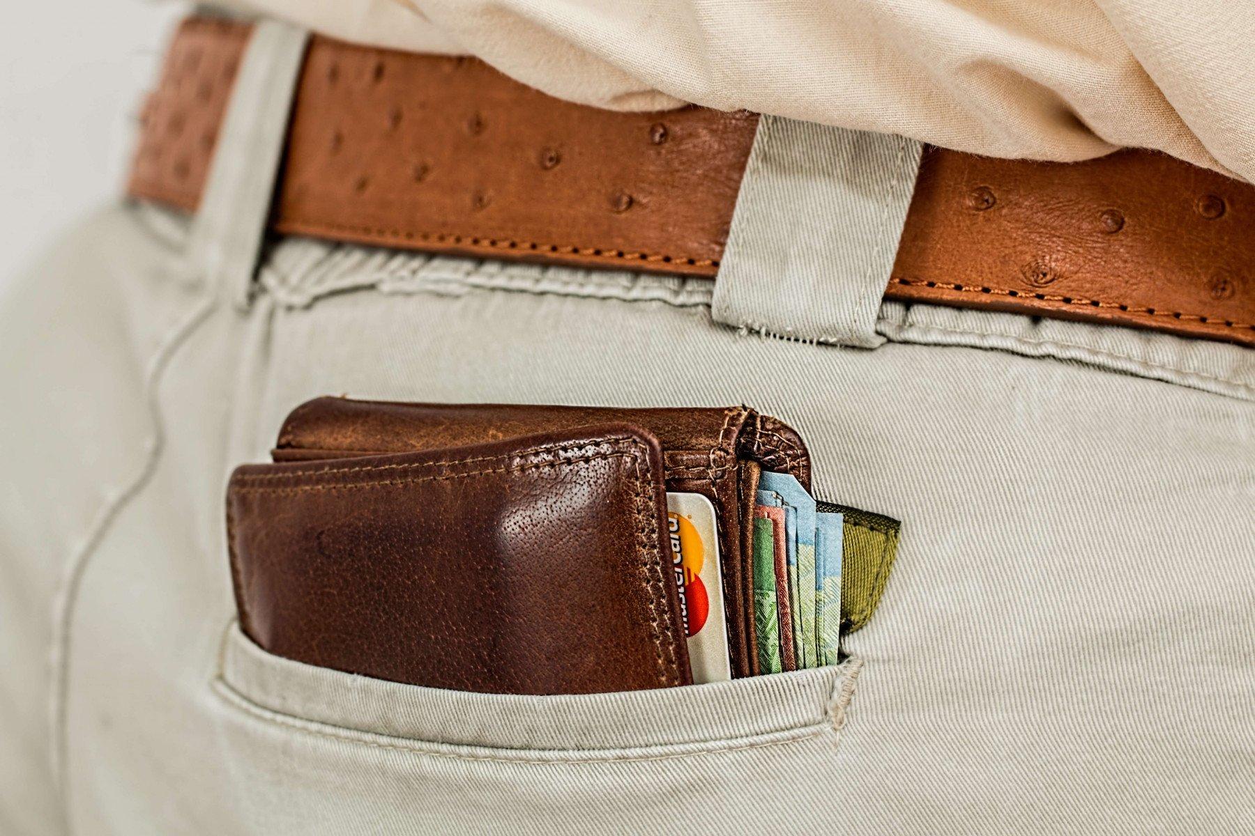 En brun skinnplånbok i bakfickan på ett par byxor