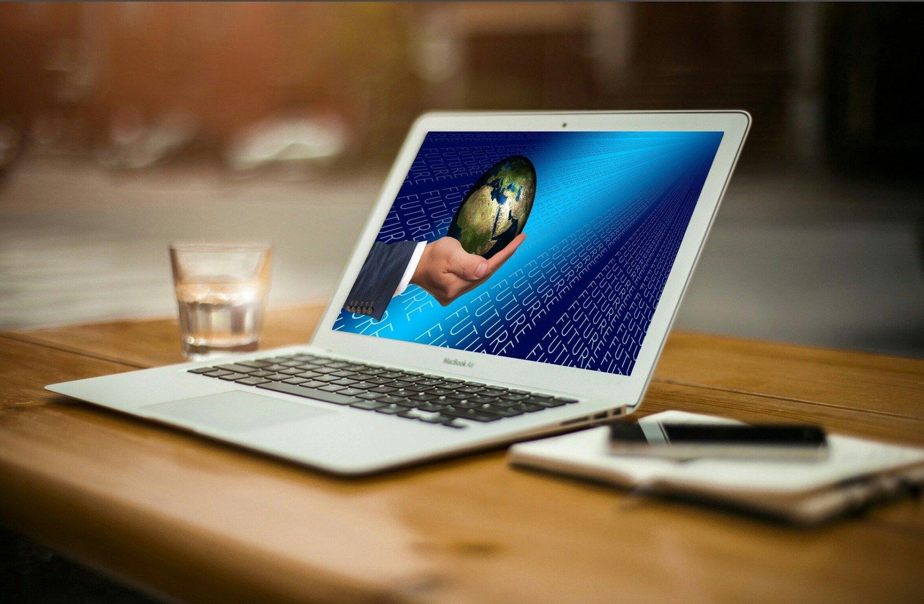 Laptop uppställd på ett bord med en skärmsläckare som föreställer en hand som håller i en jordglob
