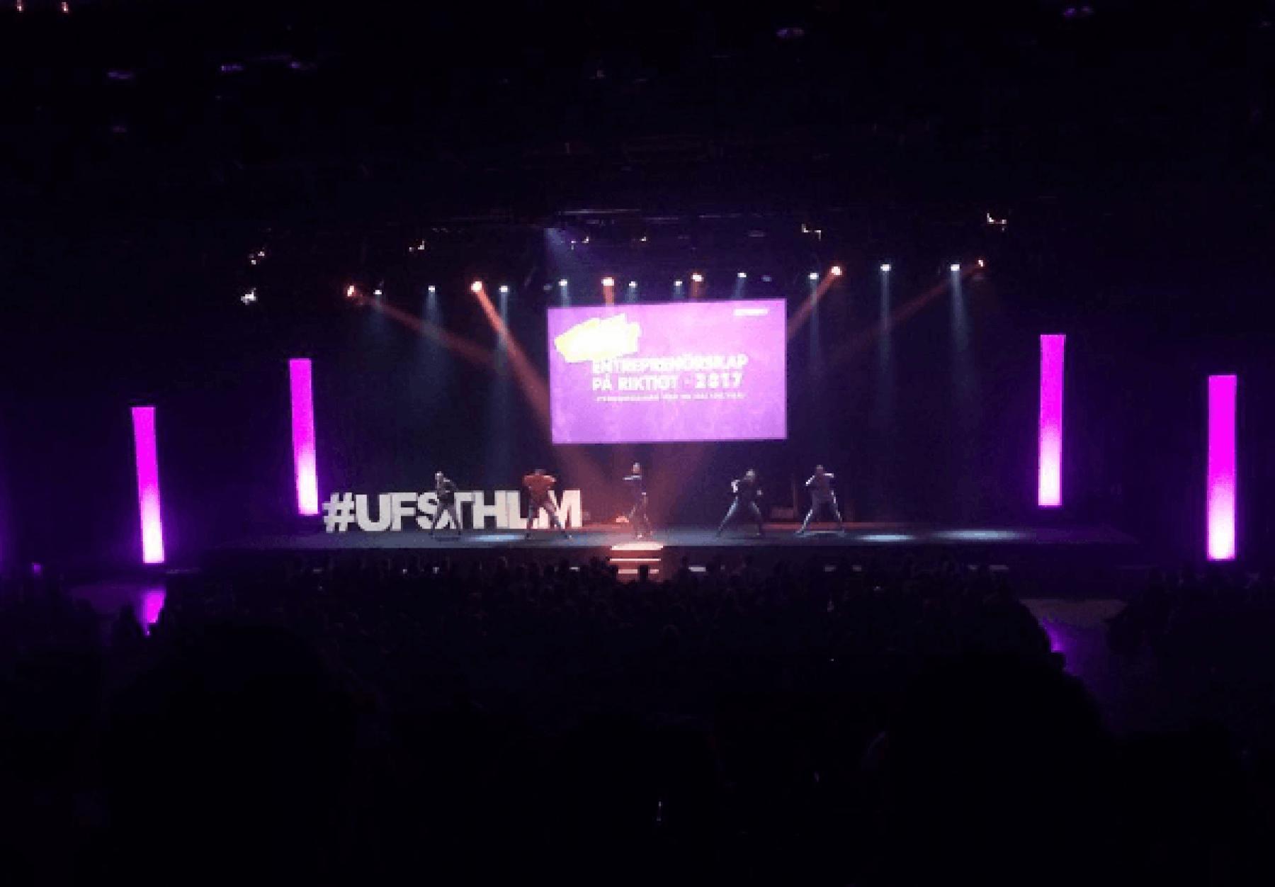 UF Sthlm står på en scen och håller i en presentation