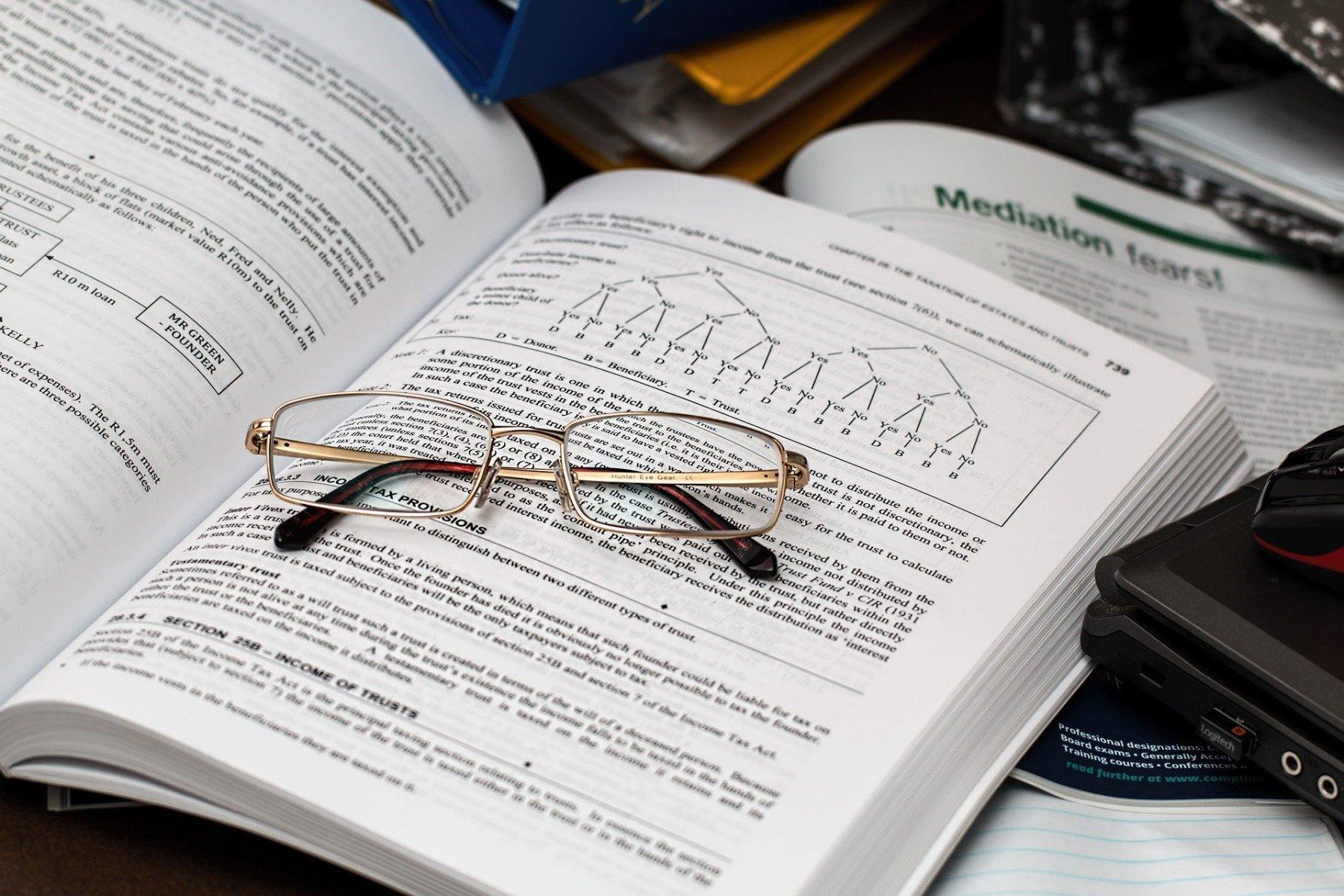 En uppslagen ekonomibok med ett par läsglasögon som vilar på den.