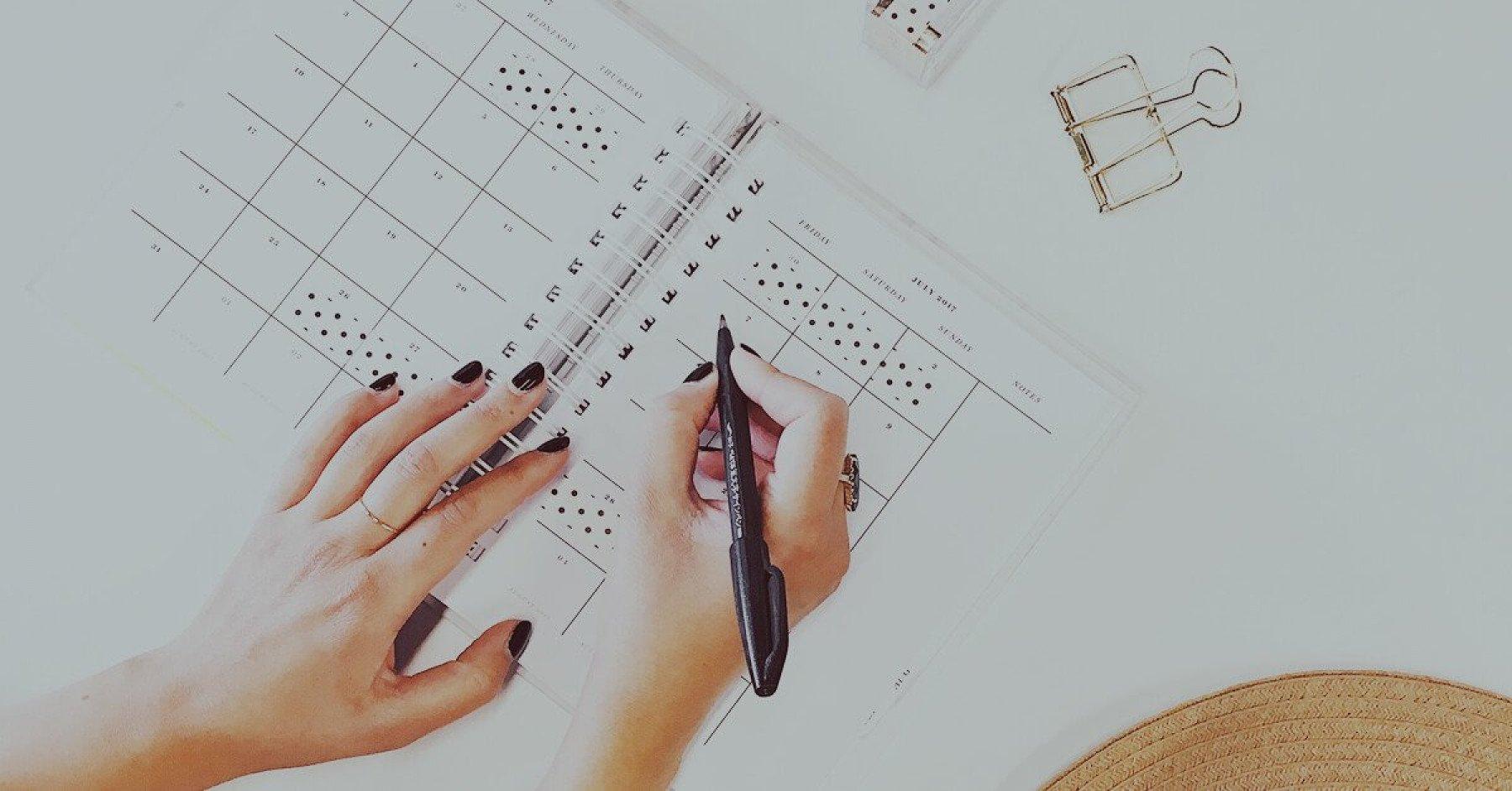 Händer som skriver i en kalender.