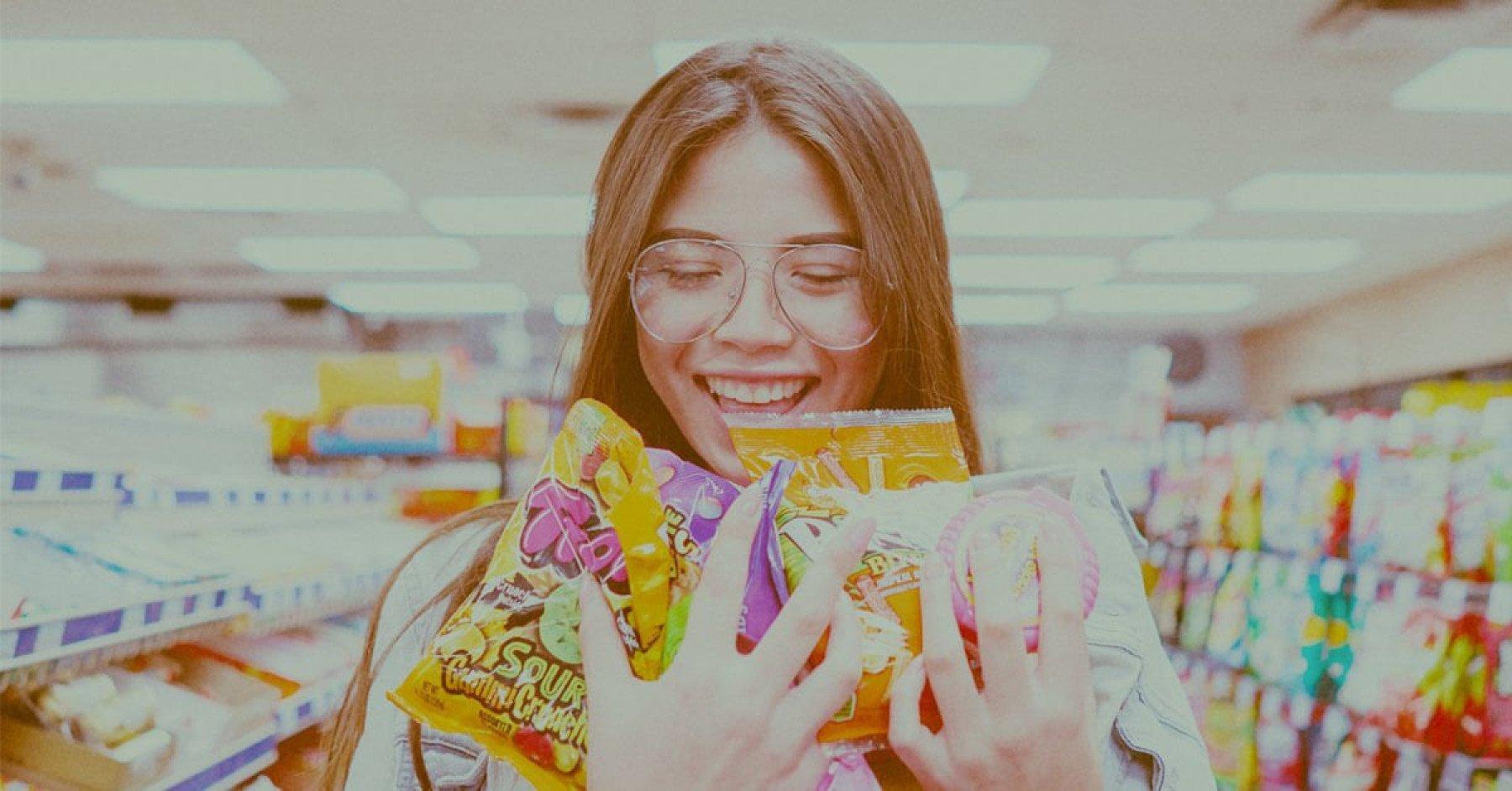 En ungdom står i en kiosk och håller i ett gäng godispåsar i sin famn